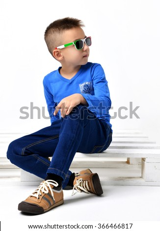 Fashion beautiful little boy in italy sunglasses blue cloth jeans sitting over white background - stock photo