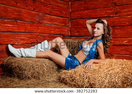 Fashion beautiful sexy cowgirl in jeans shorts and a shirt at the ranch farm. pinup and wild west western style. happy smiling slim girl on hay at farm. Fashion and pinup romantic american style. - stock photo