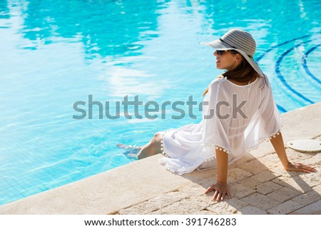 Fashion beautiful woman on summer vacation relaxing at luxury resort spa poolside. Young  fashionable lady wearing sun hat and white kaftan. - stock photo