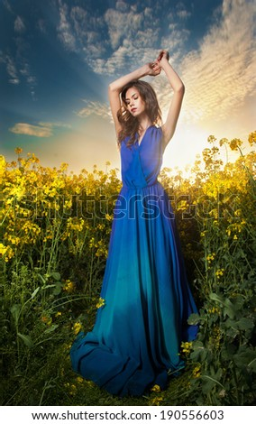 Fashion beautiful young woman in blue dress posing outdoor with cloudy dramatic sky in background. Attractive long hair brunette girl with elegant dress posing in canola field during sunset.  - stock photo