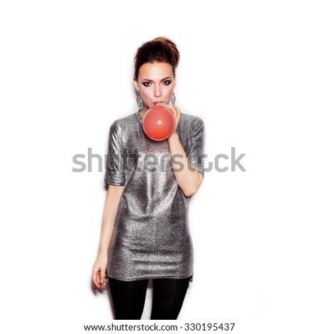 Fashion Beauty Girl blowing a red balloon. Gorgeous Woman Portrait. Stylish Haircut and Makeup. Vogue Style. On White background no isolated  - stock photo