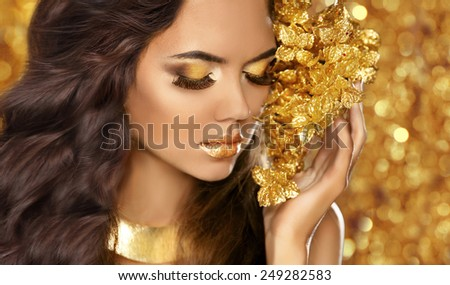 Fashion Beauty Girl Portrait. Eyes makeup. Golden jewelry. Attractive woman model with long brown hair over bokeh lights glitter background. - stock photo