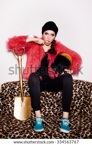Fashion Beauty Girl wearing black dress and beanie and pink fur coat licking candy. Freak young Woman sitting on leopard sofa and holding gold helmet and shovel. Vogue style indoors shot  - stock photo