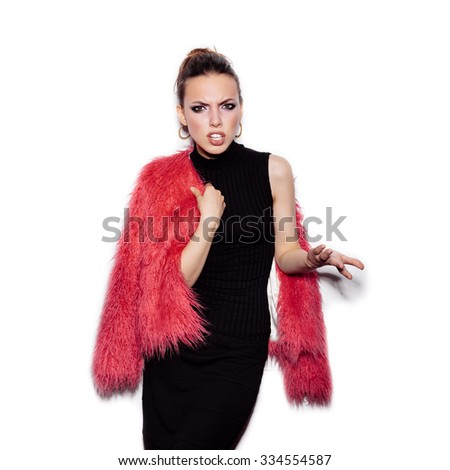 Fashion Beauty Girl wearing black dress and pink fur coat showing spite. Gorgeous young Woman Portrait. Stylish Haircut and Makeup. Vogue style studio shot on white background not isolated - stock photo