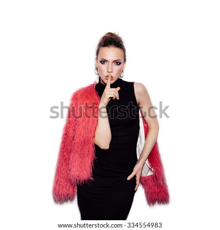 Fashion Beauty Girl wearing black dress and pink fur coat with finger on her lips showing to keep silence, hush. Gorgeous young Woman Portrait. Vogue style studio shot on white background not isolated - stock photo