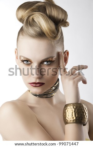 fashion beauty portrait of blond young cute girl with creative hair style and leopard make up, she is slightly turned of three quarters, looks in to the lens and has the right index finger near - stock photo