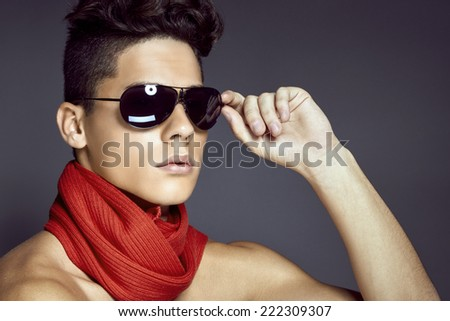 Fashion beauty portrait of sexy young man with sunglasses and scarf against blue background - stock photo
