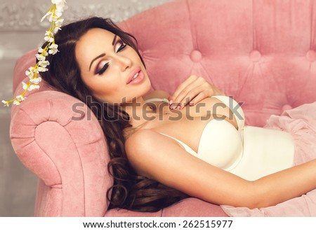 Fashion beauty portrait of tender healthy brunette woman in sexy white lingerie sleeping on a pink velvet sofa in luxury interior. Spa and healthy life concept. Bride. Perfect nude make up - stock photo