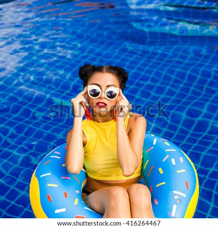 Fashion Beauty Swag Girl. Gorgeous Woman Portrait. Stylish Haircut and Makeup. Beauty girl with bright makeup hairstyle with horns in a sexy bikini swims on an inflatable circle, stylish accessories - stock photo