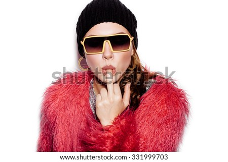 Fashion Beauty Swag Girl wearing silver dress, pink fur coat, black beanie hat. Stylish Haircut and Makeup. Young sexy Woman sucking middle finger on white background no isolated - stock photo