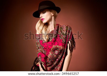 Fashion beauty woman in stylish hat, colored cashmere shawl. Autumn winter model blond girl with long blonde wavy hair, ethnic pattern headscarf. Unusual creative attractive people. Retro Vintage - stock photo