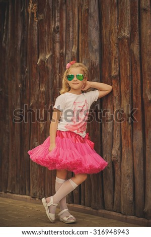 Fashion blond little girl in a pink fluffy skirt and glasses  near a wooden fence. Portrait of an adorable preschool age girl. - stock photo
