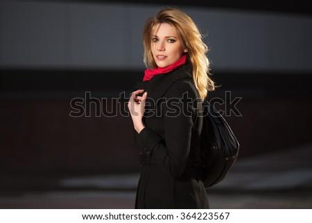 Fashion blond woman in black coat walking on night city street - stock photo