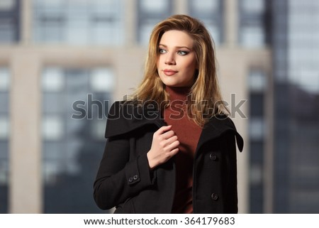 Fashion blond woman in black coat walking on the city street - stock photo