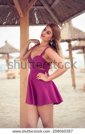Fashion blonde close up happy at the sea posing on sand under tiki patio umbrella dressed in a very sexy fuchsia pink dress - stock photo