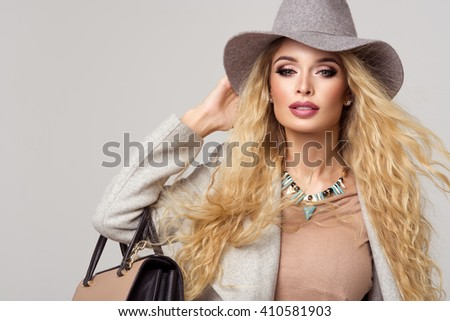 Fashion blonde model in nice clothes posing in the studio. Wearing coat, hat and handbag, ripped - stock photo