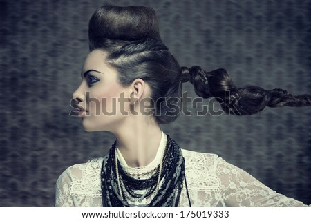 fashion brunette woman turned on profile in close-up portrait with creative hairdo and strong make-up. Wearing white lace shirt and a lot of necklaces - stock photo