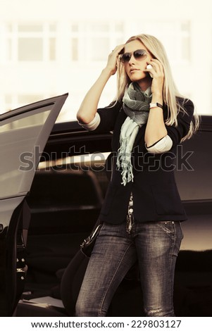 Fashion business woman calling on mobile phone at the car  - stock photo