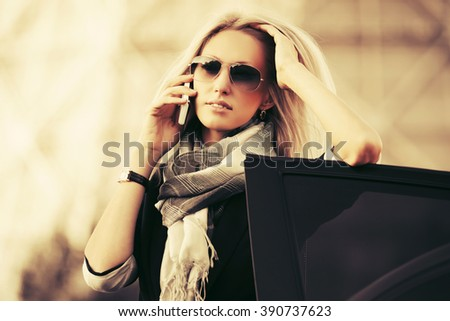 Fashion business woman in sunglasses calling on the phone next to car  - stock photo