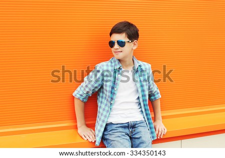 Fashion child boy wearing a sunglasses and shirt in city against orange background - stock photo