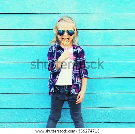 Fashion child with sweet caramel lollipop having fun over colorful blue background - stock photo