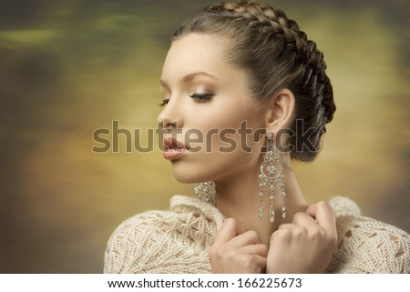 fashion close-up portrait of elegant female posing with classic hair-style, precious earrings and wool shawl   - stock photo