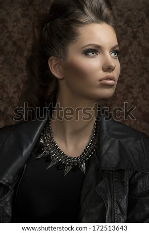 fashion close-up shoot of sensual young girl with modern gothic style and long brown hair wearing leather jacket and rock necklace  - stock photo