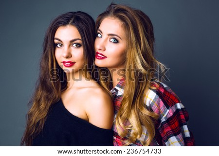 Fashion close up studio portrait of two amazing beautiful girls wearing stylish clothes, have amazing natural long hairs and bright trendy evening make up. - stock photo