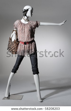 Fashion clothing on mannequin with bag on light background - stock photo