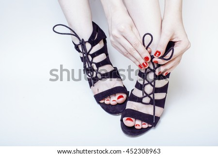 fashion concept people: woman with red nails manicure pedicure tying shoelaces on hight heel shoes isolated on white background - stock photo