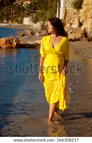 Fashion concept - Portrait of a beautiful woman with long yellow dress on a  beach. - stock photo