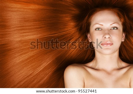 fashion concept portrait of a woman with beautiful long red healthy shiny hair - stock photo
