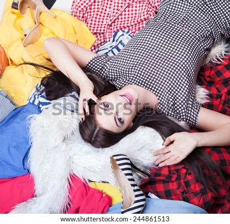 Fashion concept young attractive woman lying down on a pile of clothes and shoes - stock photo