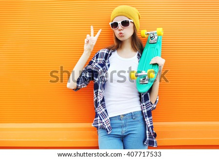 Fashion cool girl with skateboard having fun over colorful orange background - stock photo