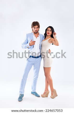 Fashion couple, men wear blue suit and woman sexy dress high heel shoes, full length over gray background - stock photo