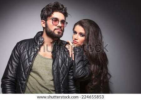 Fashion couple posing for the camera, the woman is resting of her lover's shoulder while looking at the camera, both wearing leather jackets. - stock photo