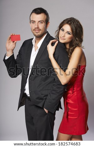 Fashion couple with blank credit card against gray background - stock photo