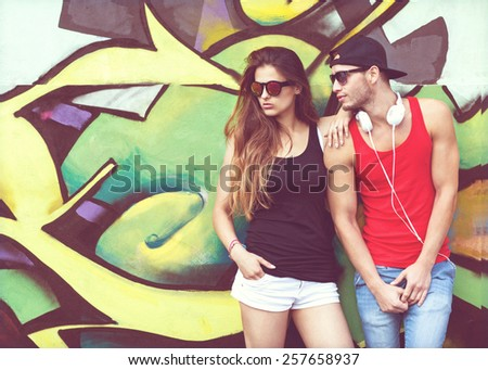 fashion couple with sunglasses near the wall graffiti - stock photo