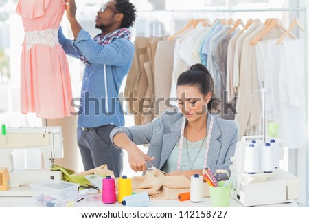 Fashion designer cutting textile at desk while her colleague adjusting dress behind - stock photo