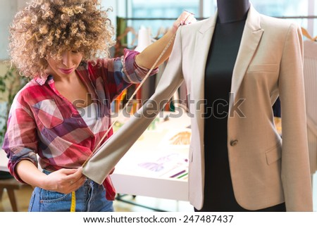 Fashion designer measuring a blazer - stock photo