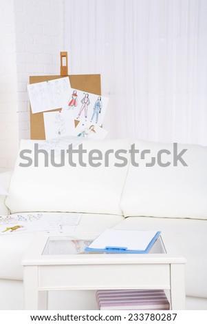 Fashion designer studio with professional equipment, sketches, mannequin, cloth - stock photo