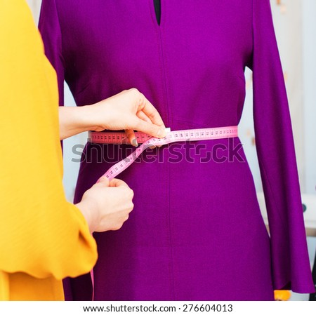 Fashion designer with measuring tape working on mannequin. - stock photo