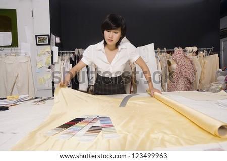 Fashion designer working at desk - stock photo