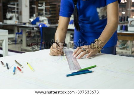 fashion designers, working in progress on tailor table in factory. - stock photo