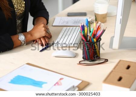 Fashion designers working in studio sitting on the desk - stock photo