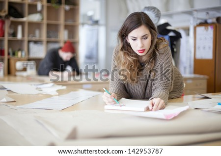 Fashion designers working in the studio - stock photo