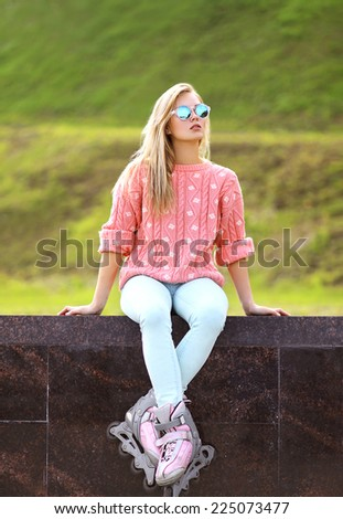 Fashion, extreme, youth and people concept - pretty stylish blonde girl in sunglasses with roller skates in the city park, cool roller girl posing outdoors - stock photo