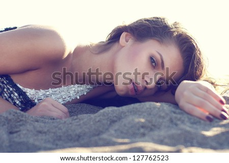 fashion face portrait of young beautiful woman lying at the sand of the beach - stock photo