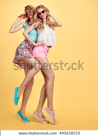 Fashion. Fashion hipster woman, fashion summer outfit having fun. Fashion sisters friends crazy cheeky emotions.Girl in fashion sunglasses, fashion wavy hairstyle posing on yellow.Unusual creative fun - stock photo