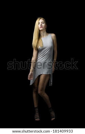 fashion female model against black background wearing grey dress blond hair  - stock photo